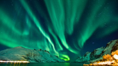 Aurora boreala in Tromso, chiar deasupra unui fiord norvegian