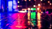 Luminile multicolore ale unui club de noapte se reflecta in trotuarul ud