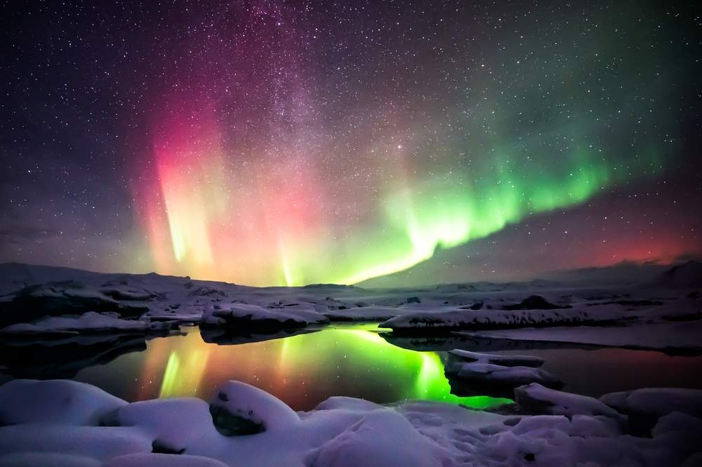 Dans de lumini verzi si rosii deasupra lagunei Jokulsarlon din Islanda