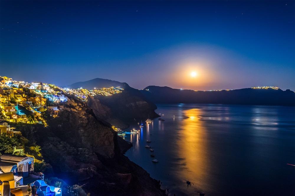 Acolo unde orasele umane se imbina armonios cu frumusetea naturii, precum in Santorini (Grecia), luna nu face decat sa lumineze peisajul mirific