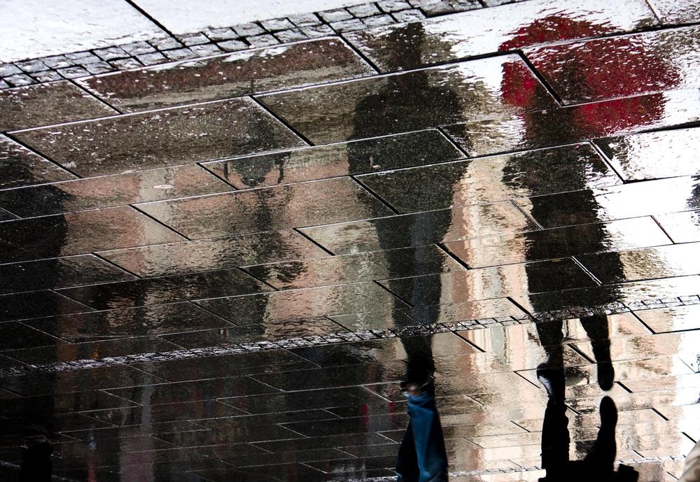 Plimbare in ploaie: Umbre ale unui cuplu reflectate in asfalt