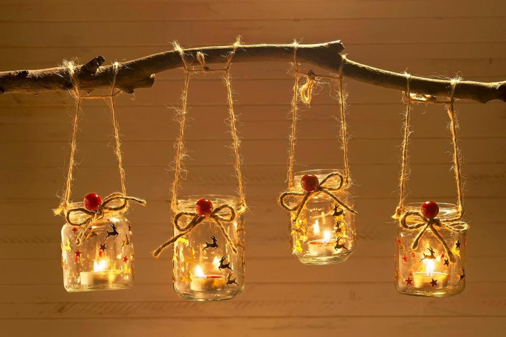 Suport de lumânări suspendate realizate din borcane reciclate și decorate cu sfoară și aplicații tematice de Crăciun