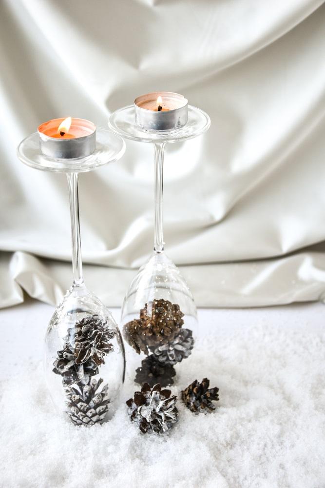 Suport decorativ de lumânări realizat din pahare de șampanie întoarse invers și umplute cu conuri de pin vopsite cu alb