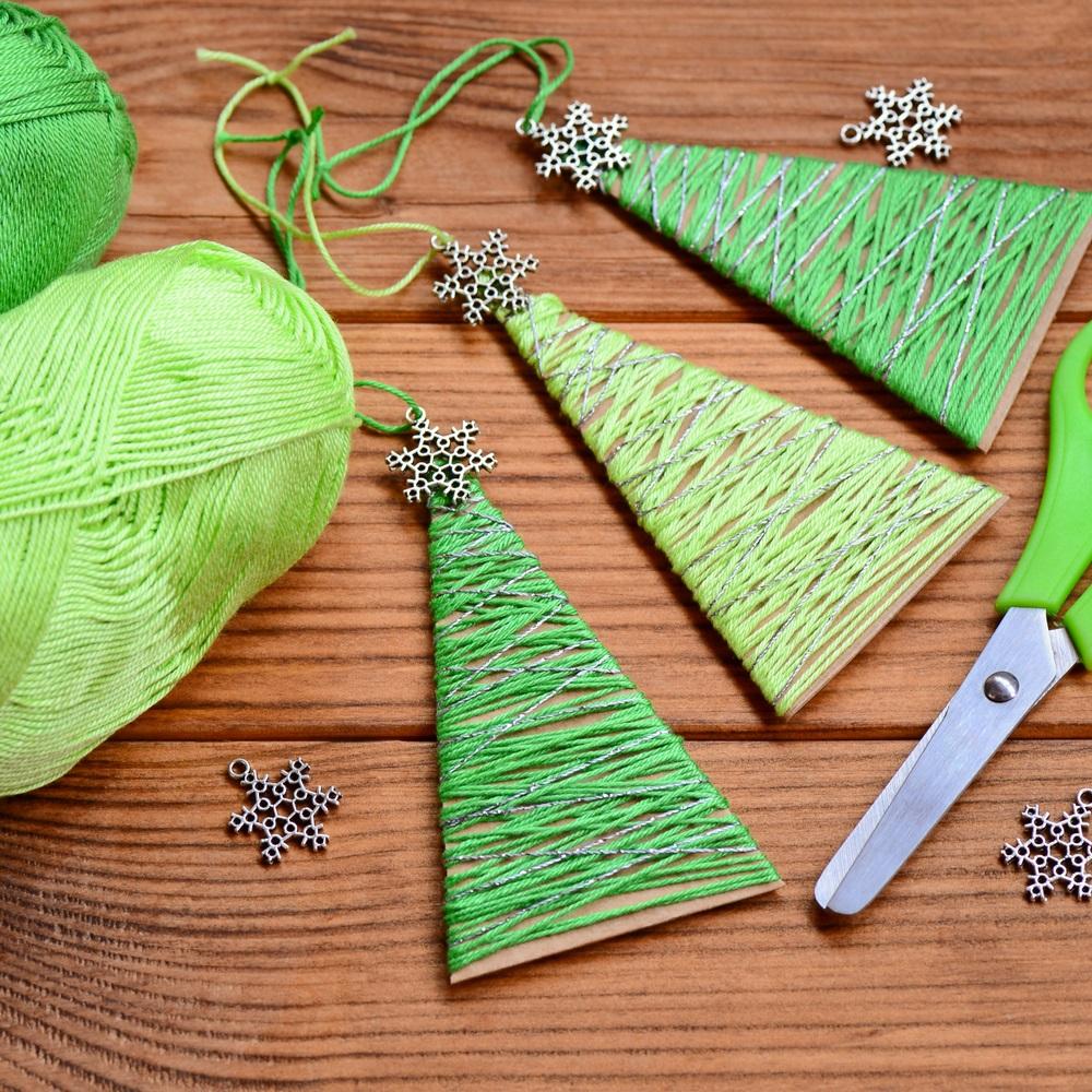 Brăduți alternativi din carton reciclat și decorați cu ață și mini fulgi de zăpadă din metal, de agățat în pomul de Crăciun