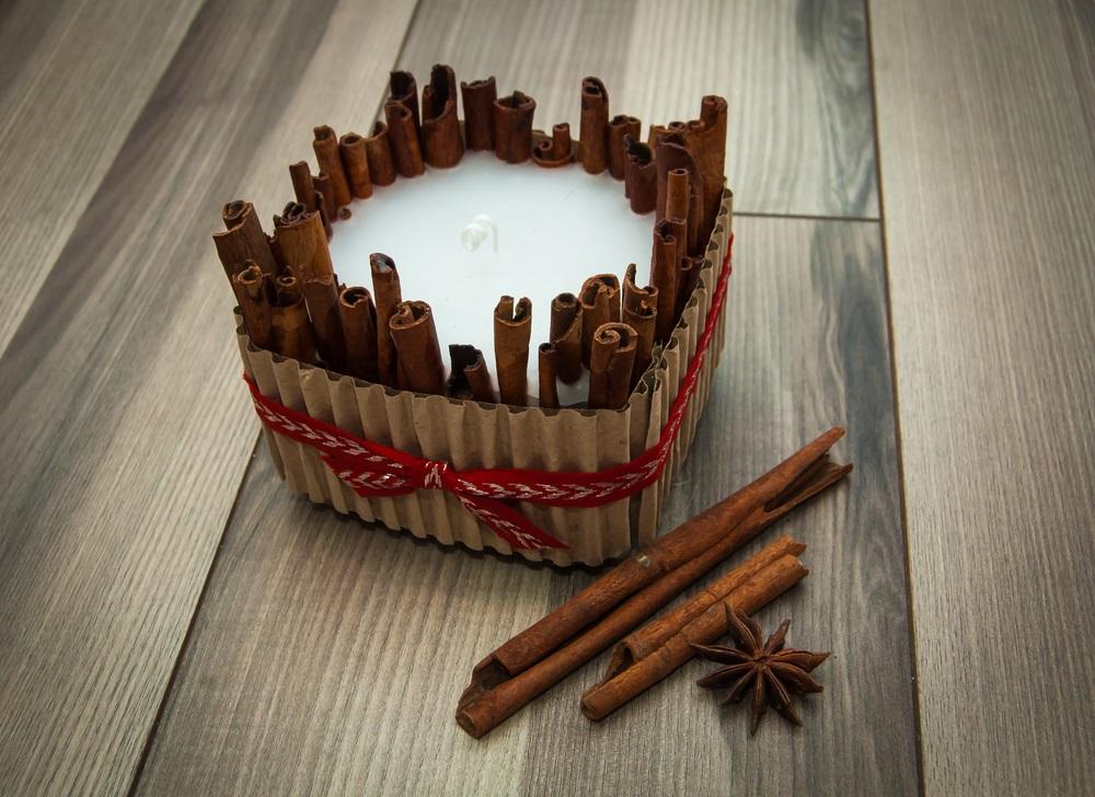 Lumânare handmade în suport de bețe de scorțișoară și carton decorat cu panglică