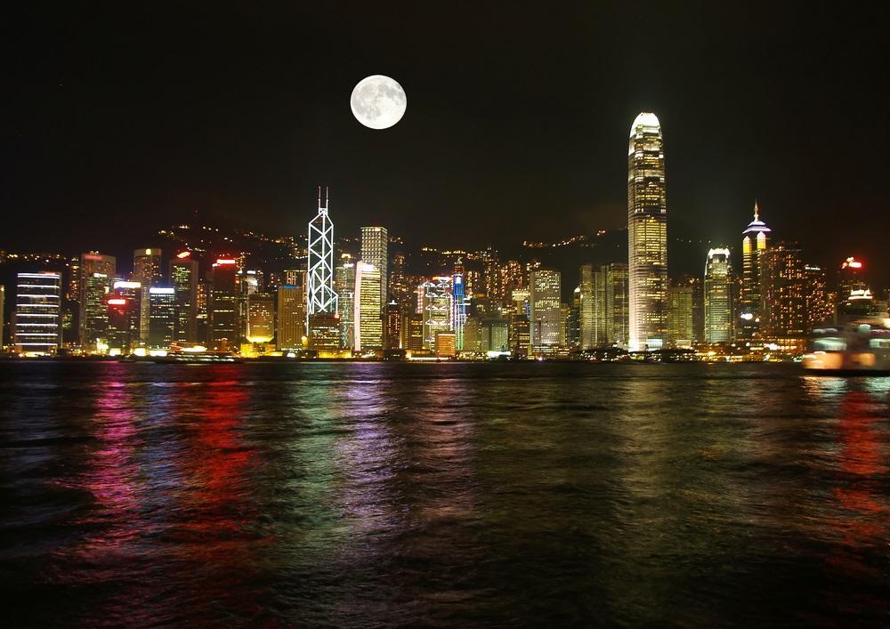 Reflexia lunii in apele care inconjoara Hong Kong formeaza un peisaj urban aproape magic
