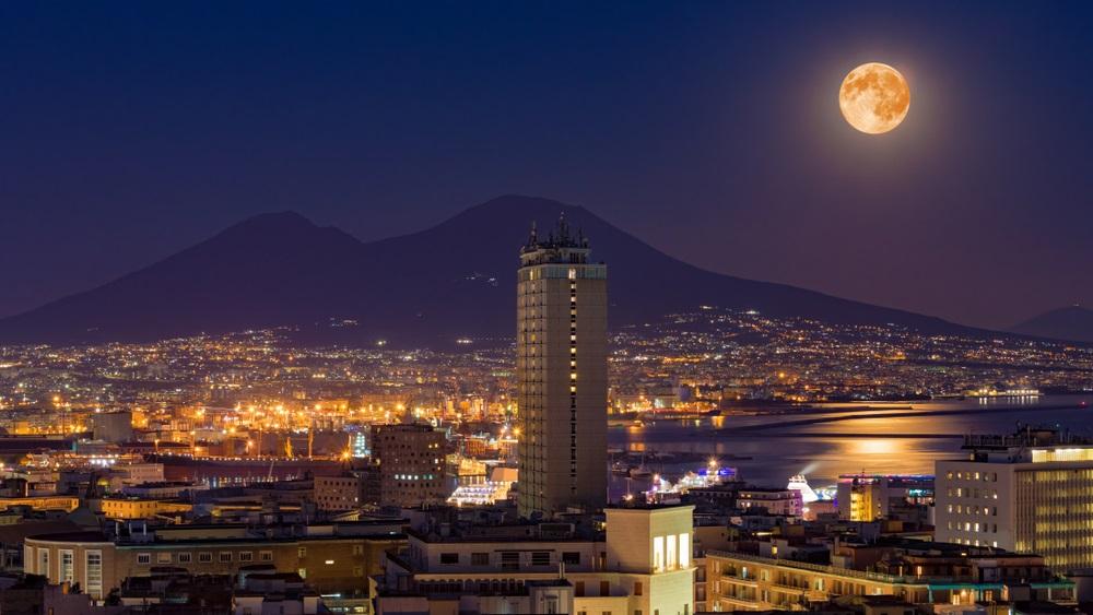 Luna plina se reflecta duios in apele calme ale marii.  Imaginea surprinde luna plina deasupra muntelui Vezuviu si a orasului Napoli (Italia)