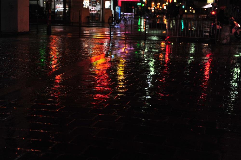 Luminile neoanelor colorate reflectandu-se pe strazile udate de ploaie ale Parisului